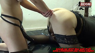 German crossdresser during anal fisting from mature femdom with big strap on dildo