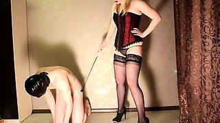 Slender blonde dominatrix in stockings punishes her slave