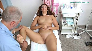 old doctor takes care of brunette in his gyno ward