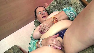 Chubby mature lady oiling up her tits and toying her pussy